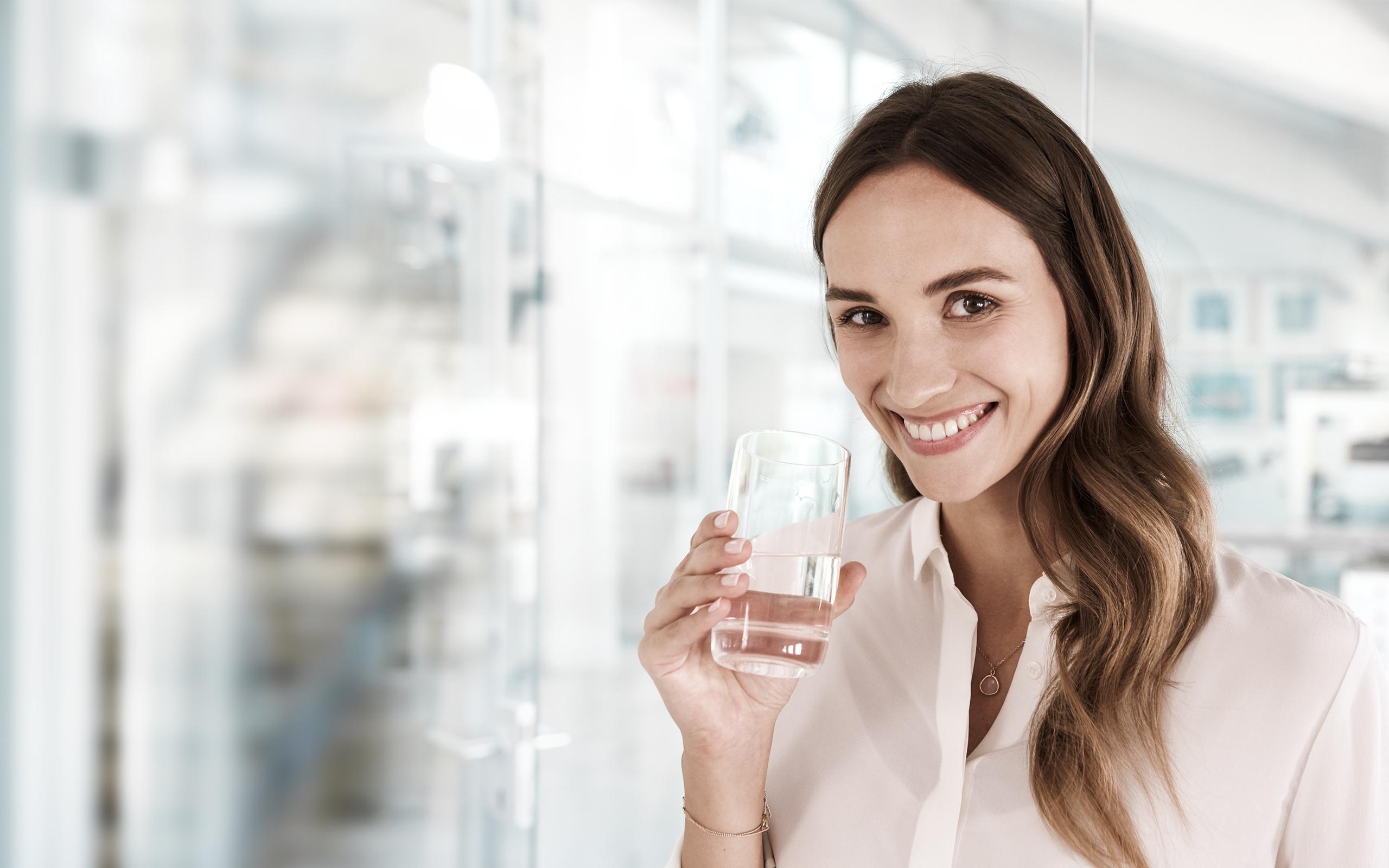 BRITA Abfallvermeidung Frau im Büro mit Wasser